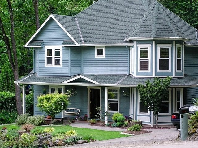 blue two-story house with a gray roof and white trim